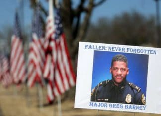 A sign and flags honor Riverdale Police Maj. Greg Barney, who was not wearing a bulletproof vest when he was shot